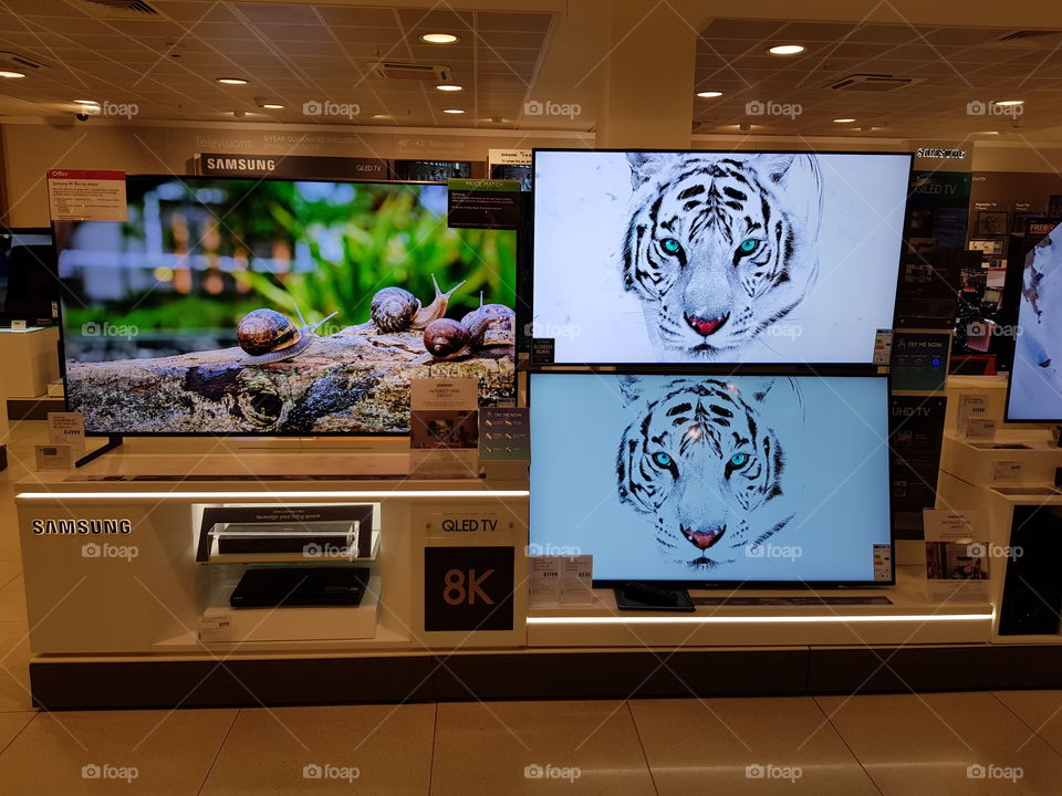 Samsung QLED television 8K and 4K UHD TV displaying comparison wall mounted TV