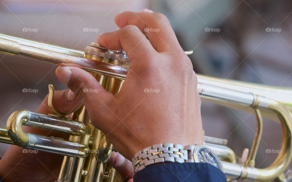 A closeup of a youth's hands playing the trumpet.