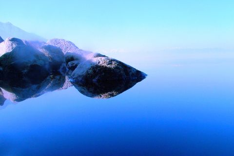 This is actually several stones sitting in the water and the reflection of those rocks and sky - the sky and water are so still and the color so seemless, you cannot tell where the skyline and the waterline meet. and the rock looks like one , when it's only rock and reflection.