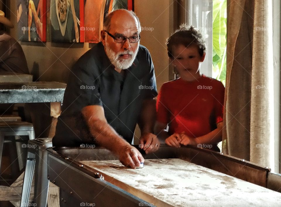 Grandfather And Grandson. Grandfather Playing Shuffleboard With Young Grandson