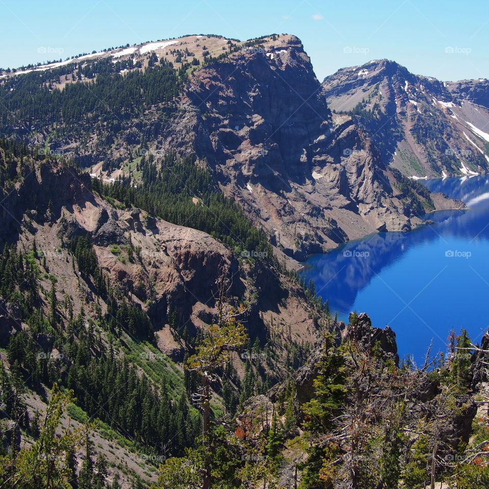 The jagged rim reflecting into the rich blue waters of Crater Lake in Southern Oregon on a beautiful summer morning with perfect clear blue skies.