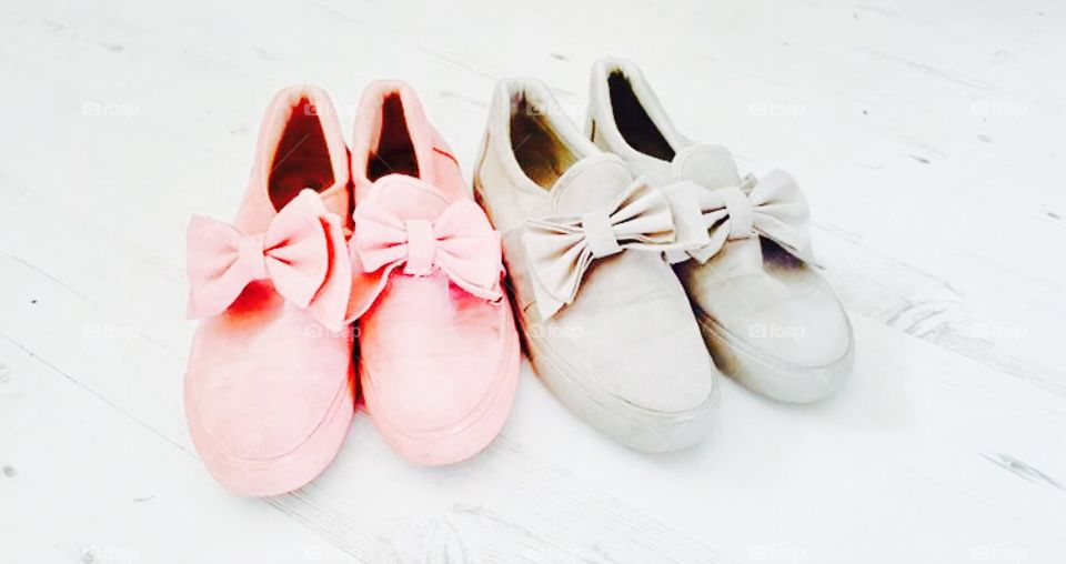 Pink and grey ladies fashion shoes on a plain white background with bows