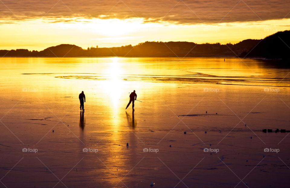 Skaters on frozen fjord.
