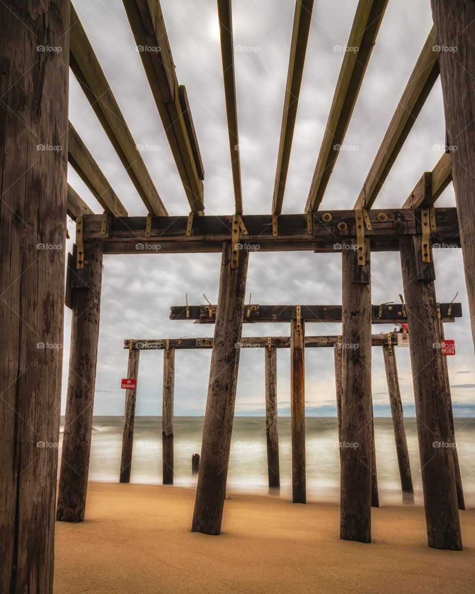 Beams of an old wooden pier leading into the ocean criss crossing to create geometric shapes, framing a moody stormy sky.