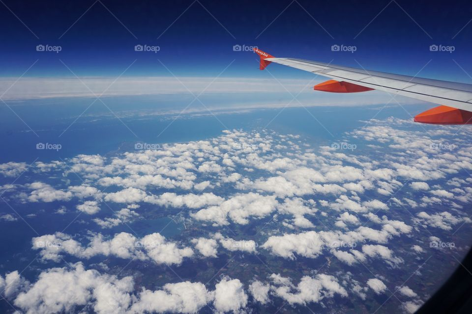 Window view from an Easy Jet Aeroplane.. puffy white clouds with a bright blue sky and glimpses of land below ..