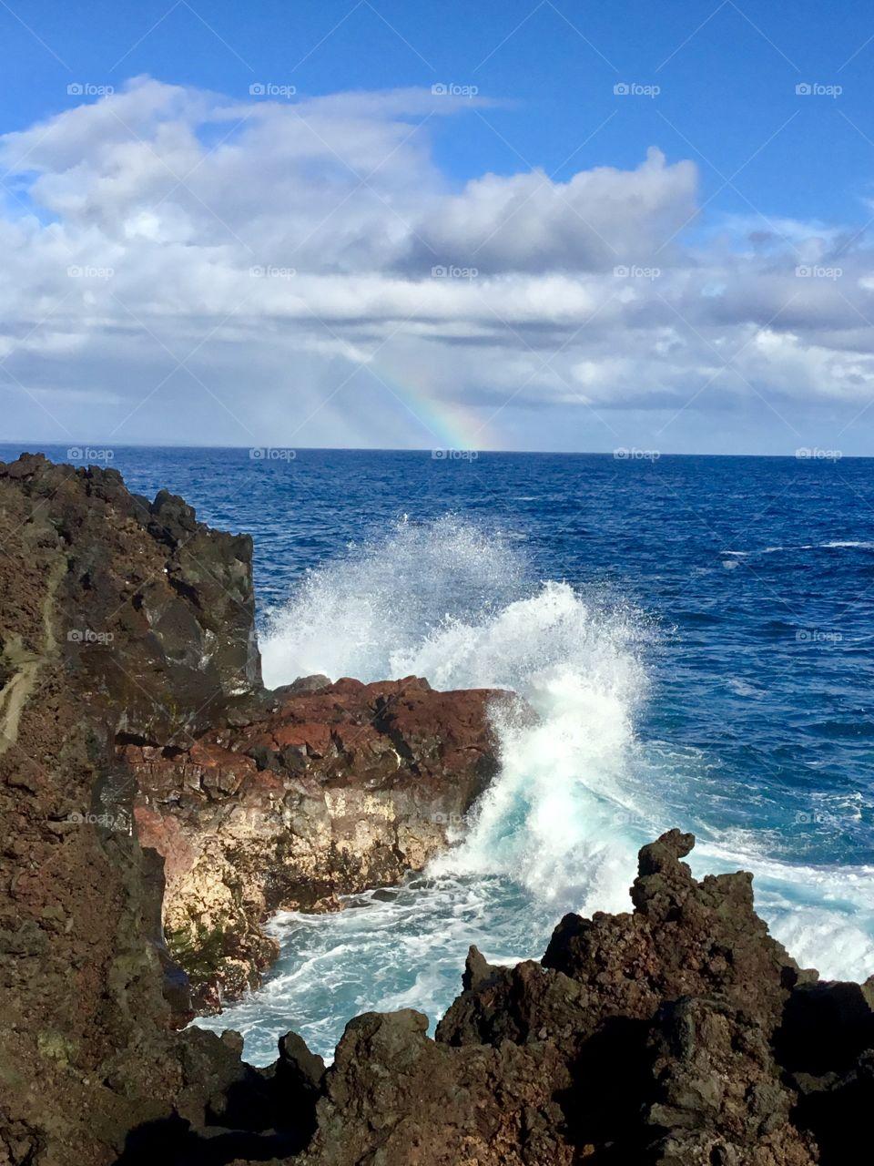 Splash in the foreground, rainbow on the horizon