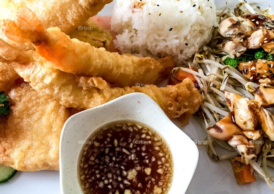Japanese meal on plate including prawn and vegetable tempura, sushi, sashimi, maki, salmon, veggie, teriyaki, steamed rice, tempura sauce