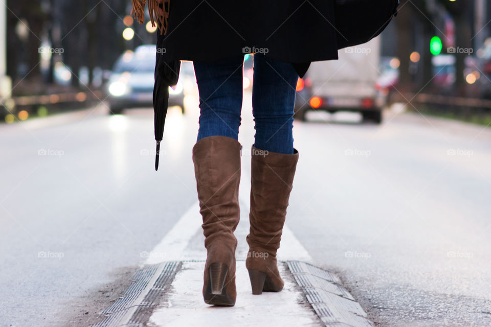 Woman in boots walking in the middle of the street