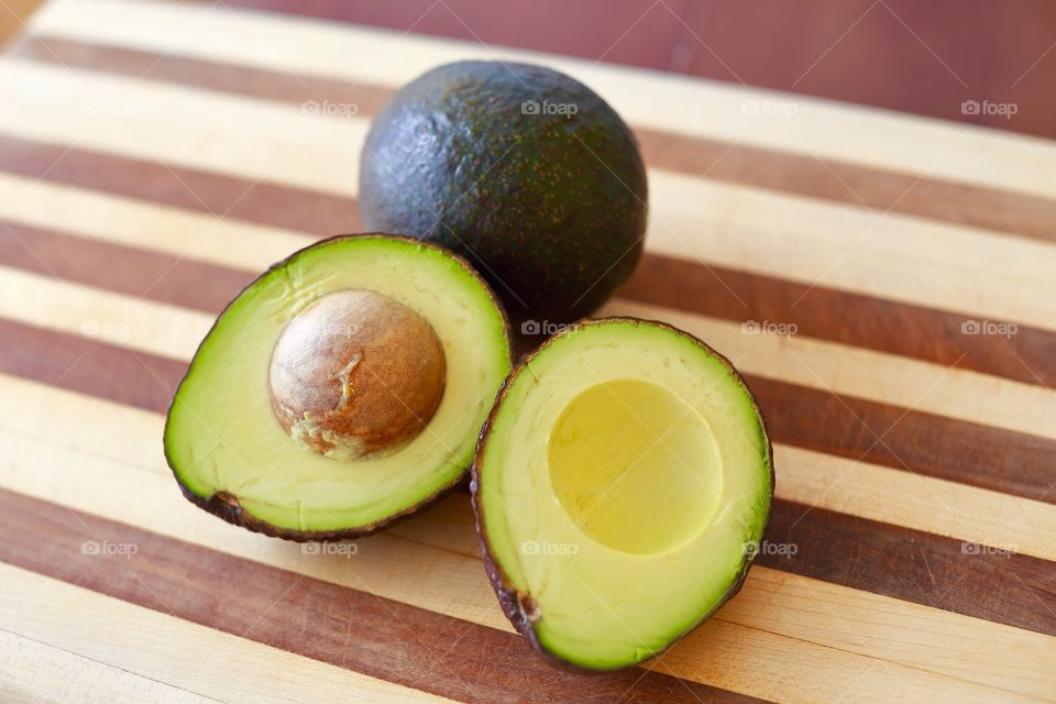 Avocados on a cutting board for a healthy snack.