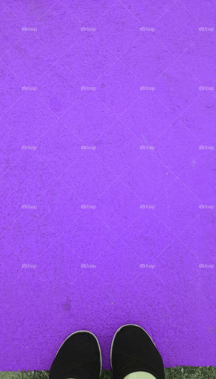 Person standing near purple background