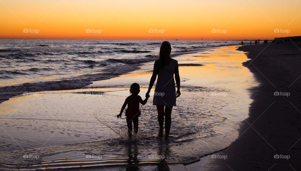 Silhouette of mother and daughter walking on beach