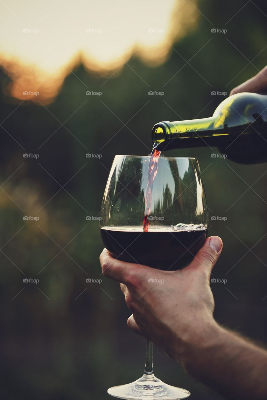 Close-up of hand pouring wine in wine glass