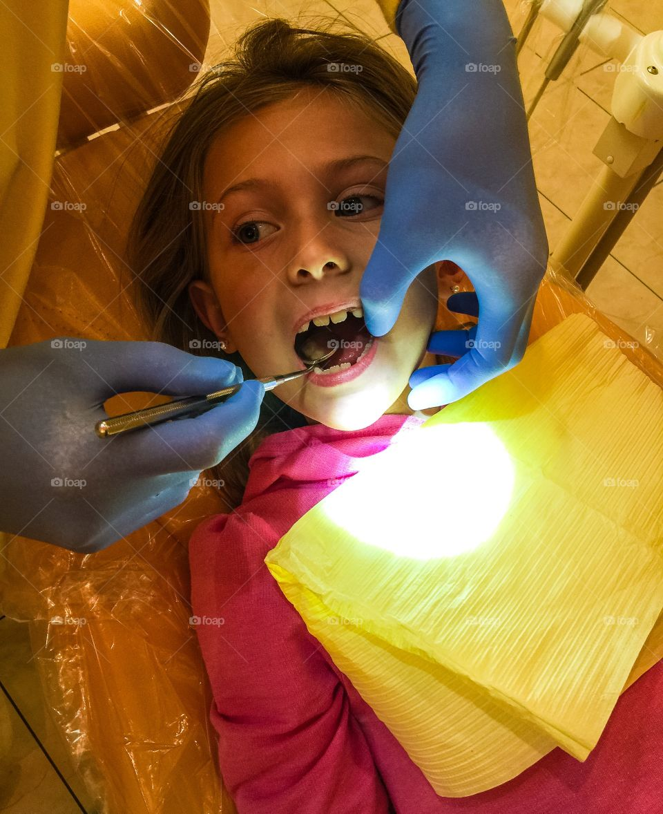 Close-up of girl with open mouth at dentist