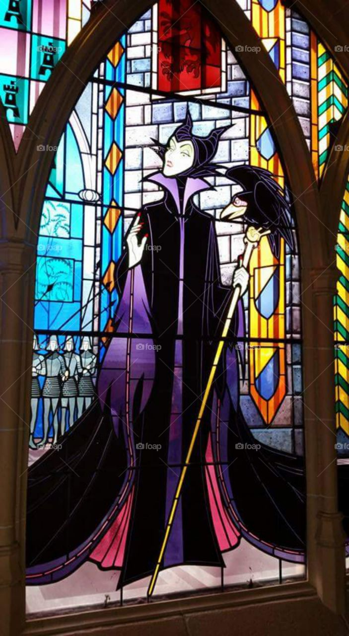 "maleficent window  Disney land Paris / Euro Disneys   one of Sleeping beauty castles  stain glass window   (series available  )  Maleficent (/məˈlɛfɪsənt/ or /məˈlɪfɪsənt/) is the main antagonist of Walt Disney's 1959 film Sleeping Beauty. She is characterized as the ""Mistress of All Evil"" who, after not being invited to a christening, curses the infant Princess Aurora to ""prick her finger on the spindle of a spinning wheel and die"" before the sun sets on Aurora's sixteenth birthday.   Sleeping Beauty Castle is the fairy tale structure castle at the center of Disneyland Park, Hong Kong Disneyland and Disneyland Paris. It is based on the late-19th century Neuschwanstein Castle in Bavaria, Germany,with some French inspirations (especially Notre Dame de Paris and the Hospices de Beaune)."