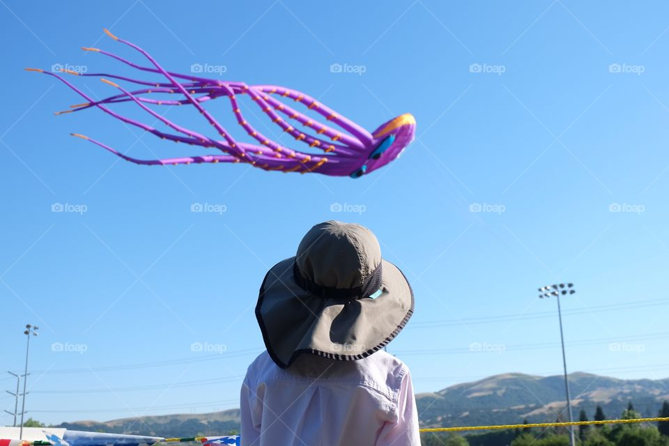 Kid in hat watching a giant colorful kite fly