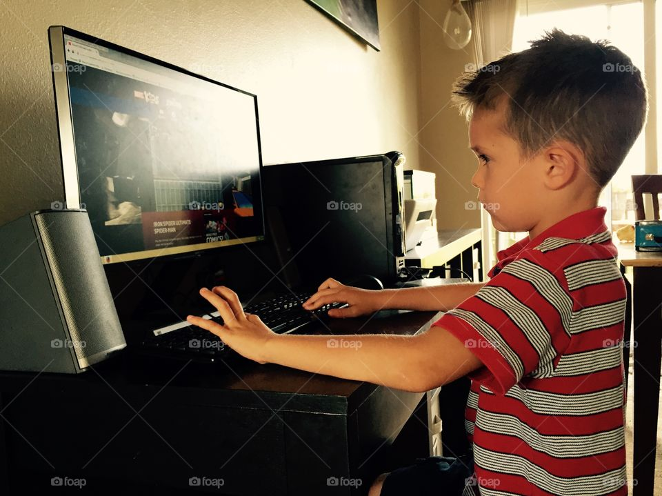 A little boy playing game in desktop
