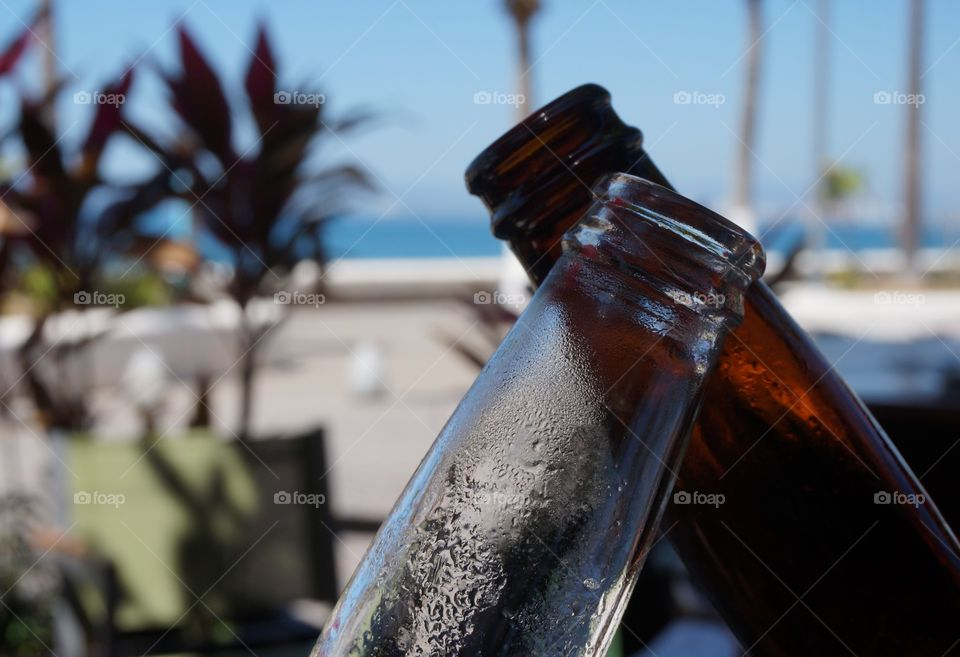 Cheers!!!  Clinking ice cold beer bottles in a toast.  Photo taken at restaurant by the beach on Mazatlan, Mexico.