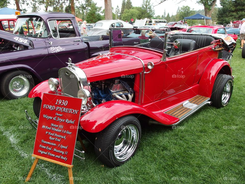A classic bright red hot rod at the annual car show in Drake Park in Central Oregon during the summer.