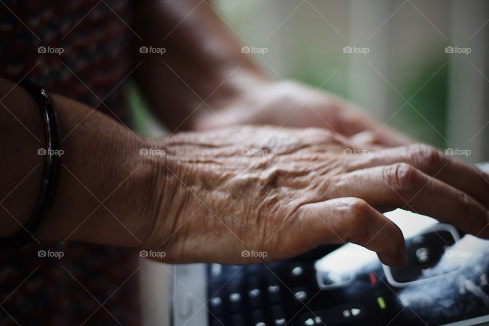 aging hand of hard working woman using tablet and learning technology