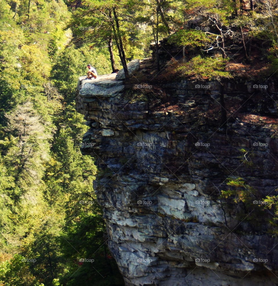 A man sitting on the edge of a cliff in Fall Creek Falls, TN.