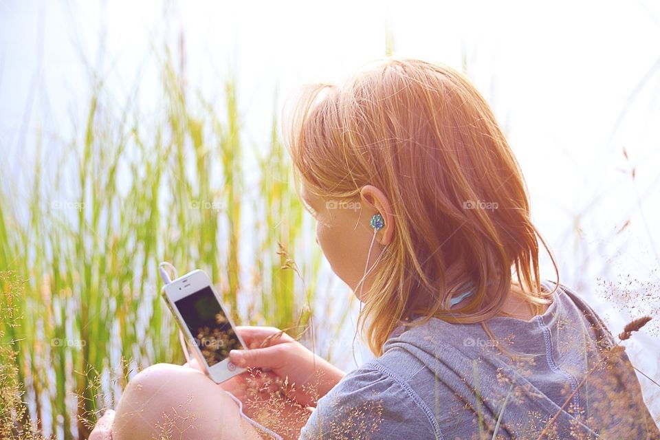 Rear view of girl holding mobile phone in hand