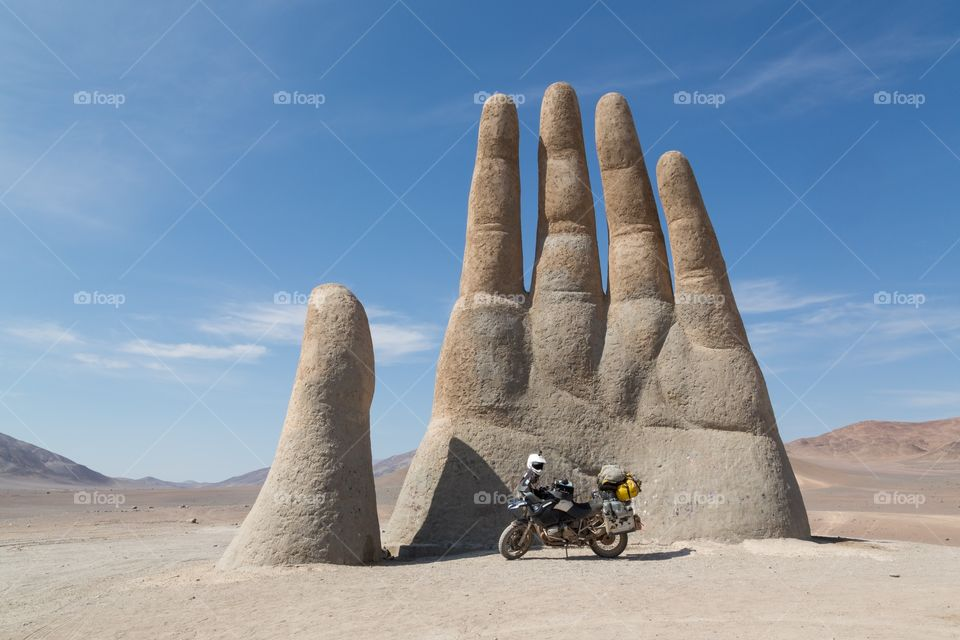 Hand of the desert. Mano del Desierto, hand of the desert statue in northern Chile. Clear blue sky. Few hills on the back ground. Motorcycle