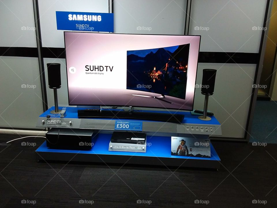 Samsung SUHD curved television displayed with soundbar and sub-woofer blu-ray player and wireless 360 speakers