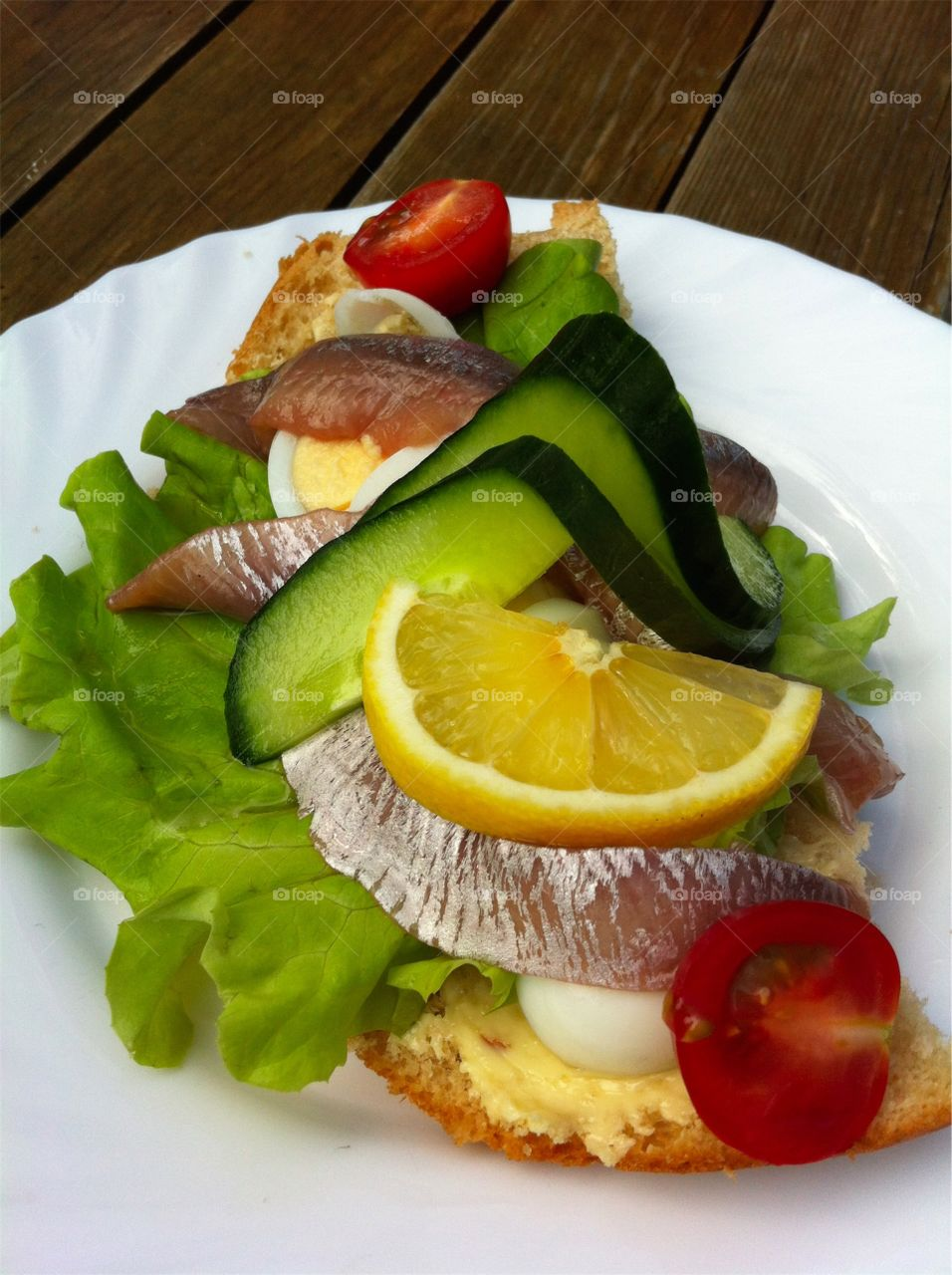 Sandwich with egg and anchovies and vegetables on white plate on wooden table outdoors.
