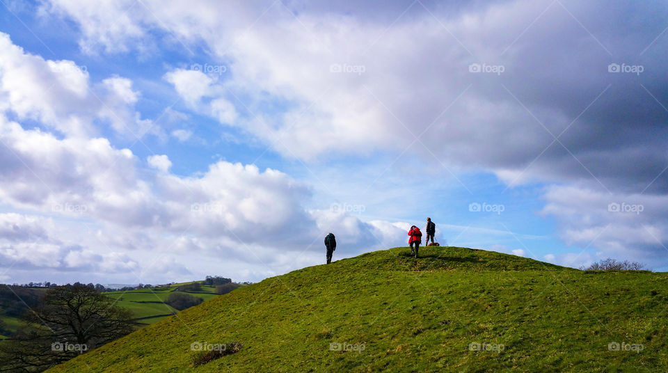 People hiking on green mountain