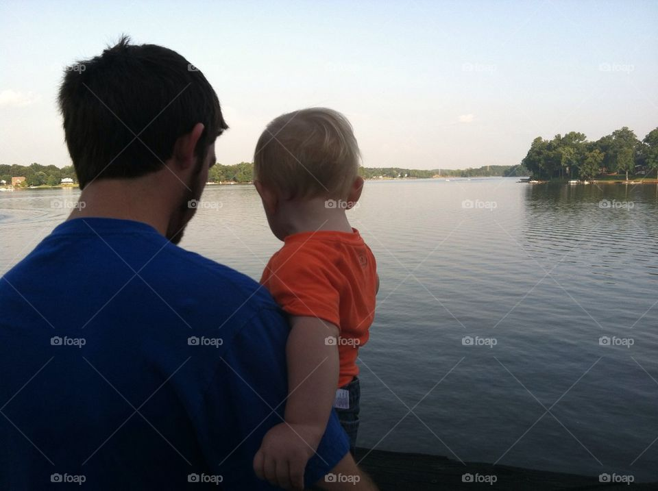 Father and son watching ducks from the dock