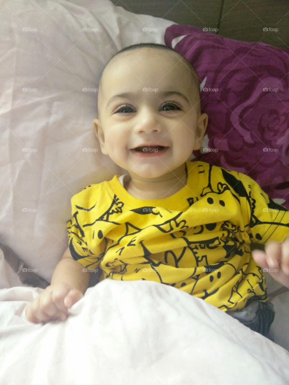 High angle view of baby boy on bed and laughing