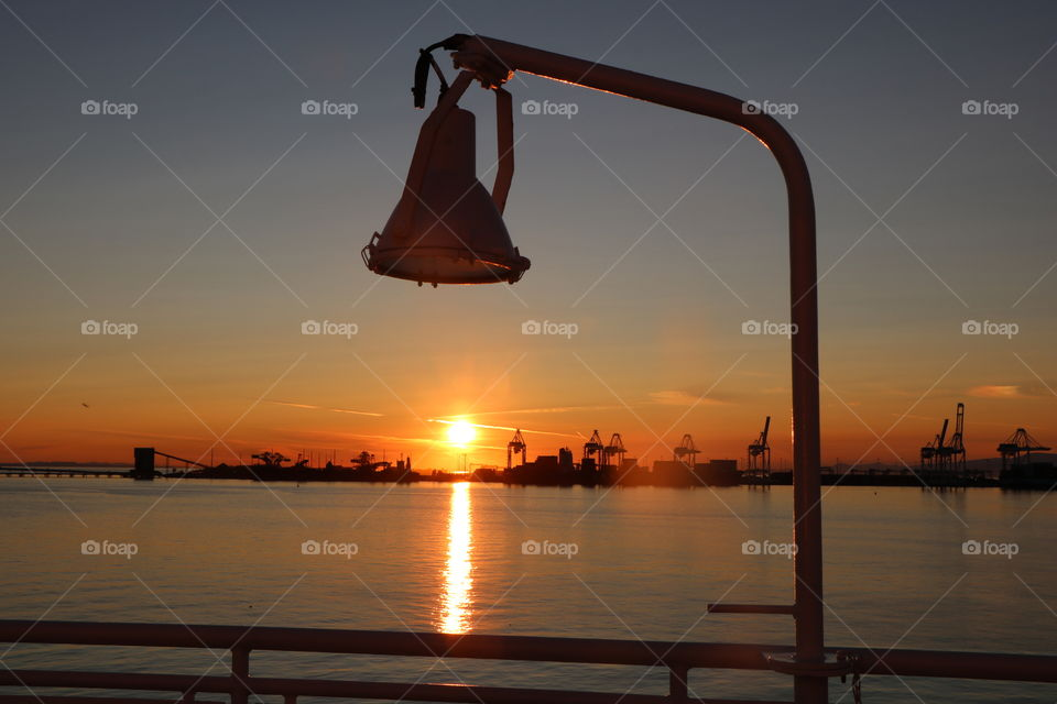 The lamppost on the dock of the boat aligned with the sunset light reflecting in the ocean .. what a nice view from the ferry ride!
