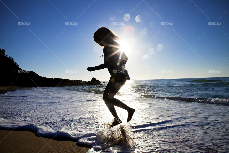silhouette of a girl jumping from the sea shore