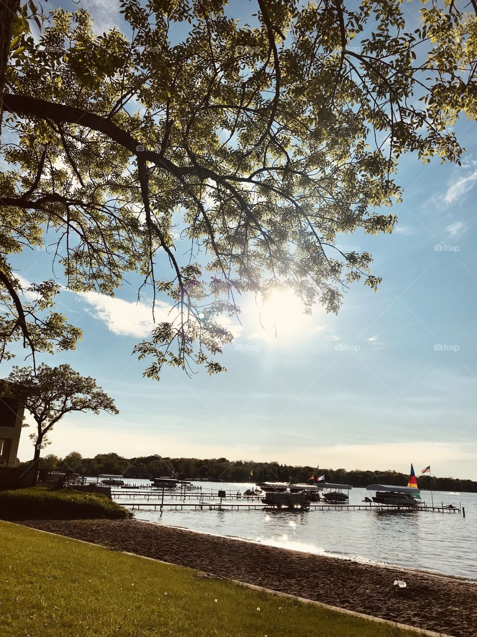 Gorgeous photo of sunny afternoon looking over beautiful lake and dock area full of boats!