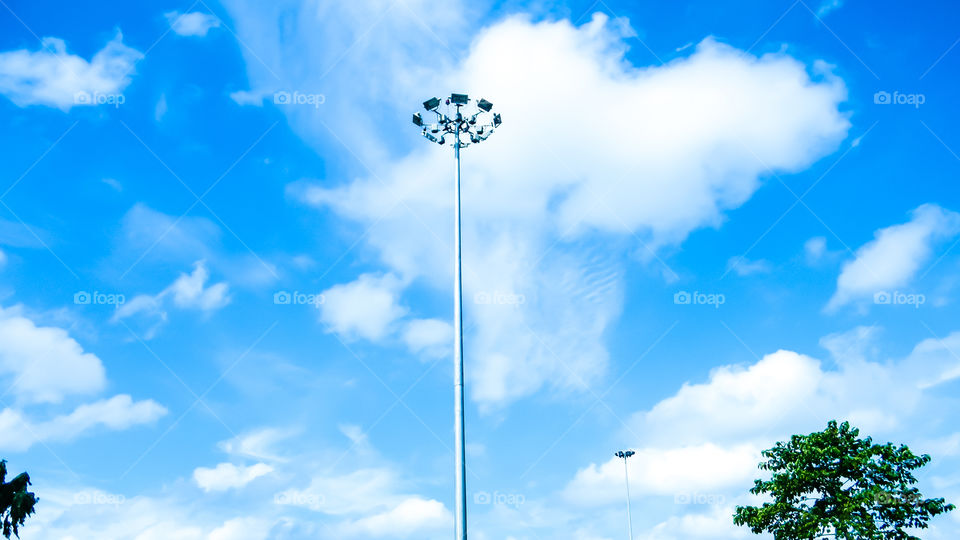 Street Public lighting pole against a blue sky and cloud background.