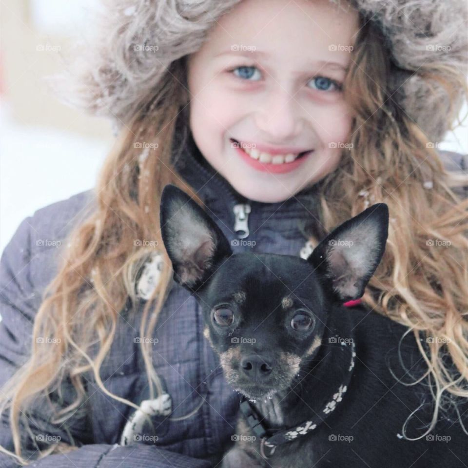 A sweet little blue-eyed girl in a faux-fur jacket holding onto her precious little Chihuahua puppy.
