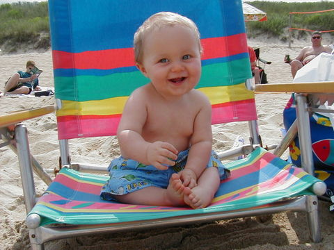 Baby at the beach. A young child sits happily on a beach chair.