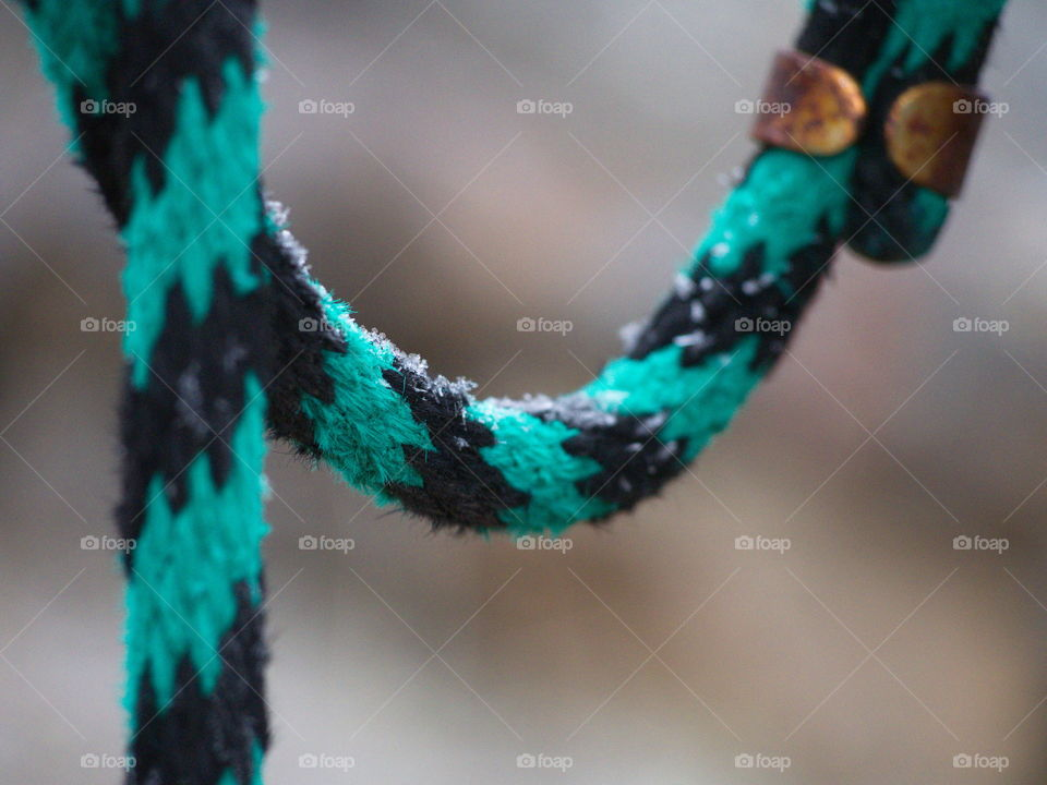 A turquoise and black striped lead rope hanging outside with a rusty clasp and a light dusting of snow