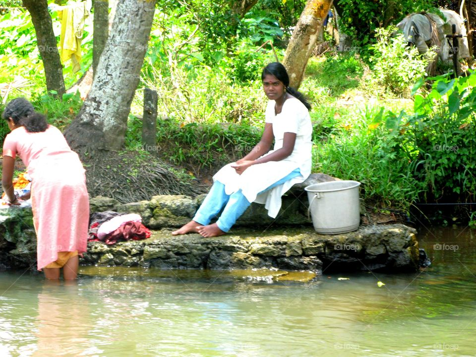 Beautiful Indian Washer Girl taking a rest into the backwater scenery of Alaphuzza, Allepey, Kerala, India