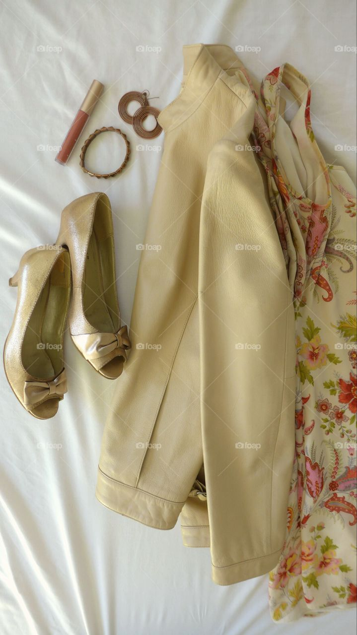 flat lay with beige leather jacket with floral dress, gold pumps, and copper accessories