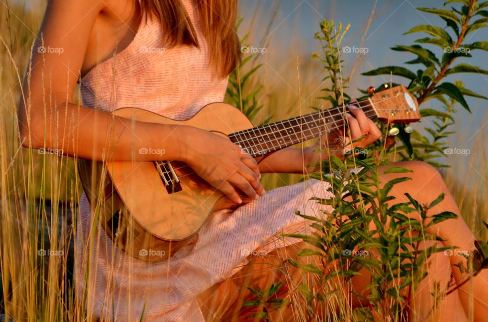 Woman playing guitar sitting outdoors