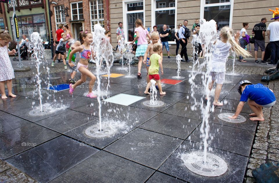 Kids playing in water fountains. In Gdansk, Poland