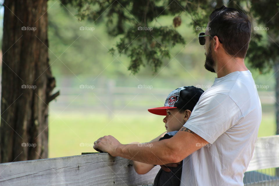 Man and son standing near fence
