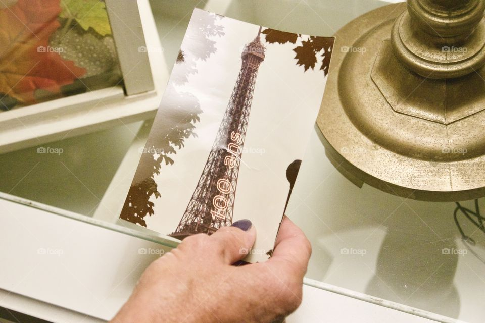 A woman looking at her old photo of when she went to Paris, France in 1989 when Paris hosted an Exposition Universelle (World's Fair) to mark the 100 year anniversary of the French Revolution. The Eiffel Tower had a special 100 Ans light on the side!