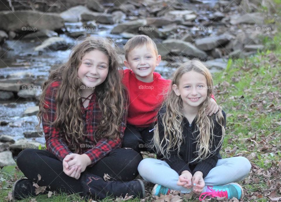 A brother affectionately hugging his two sisters in front of a beautiful mountain stream.