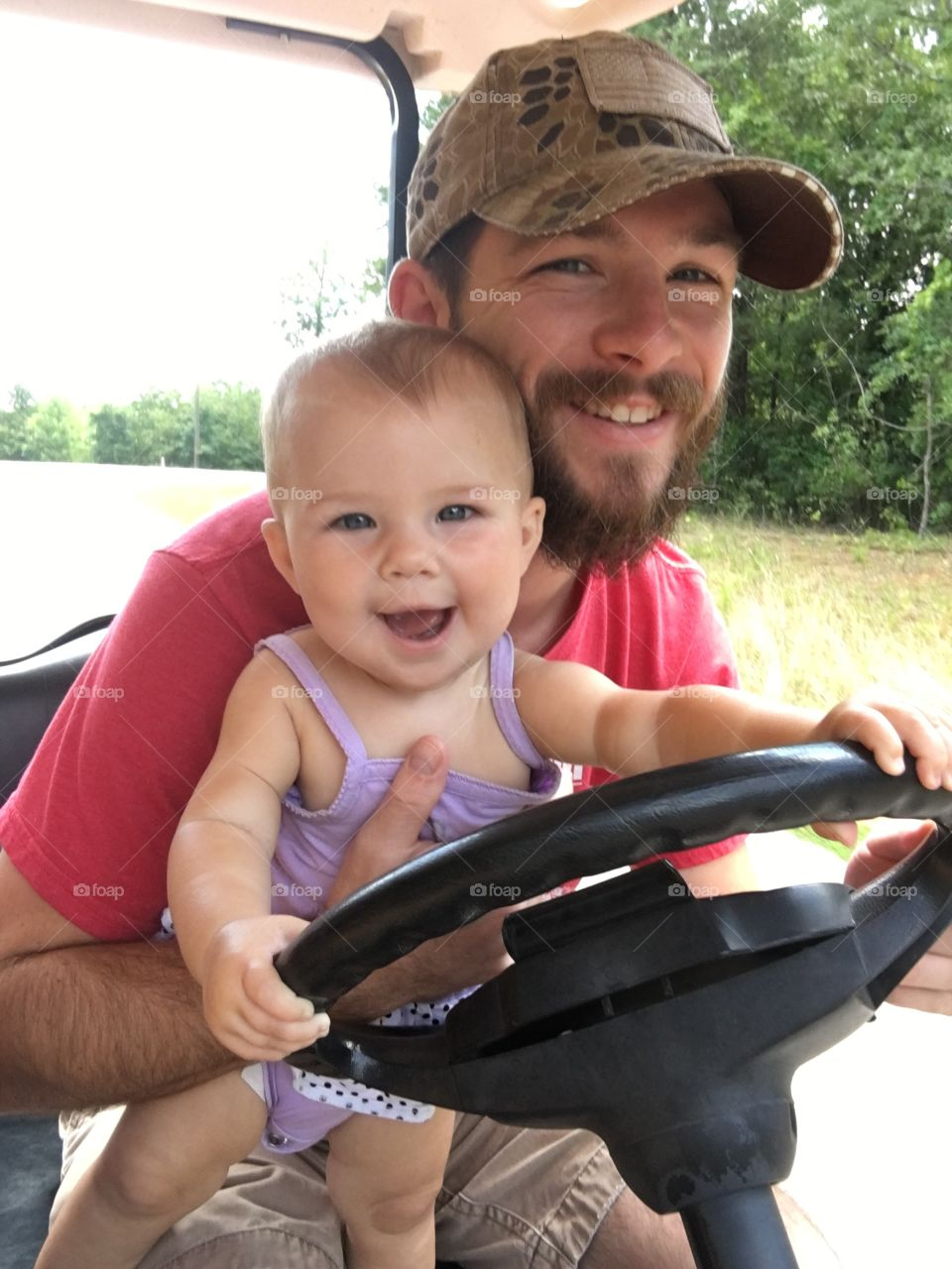 Cute baby with father holding steering wheel