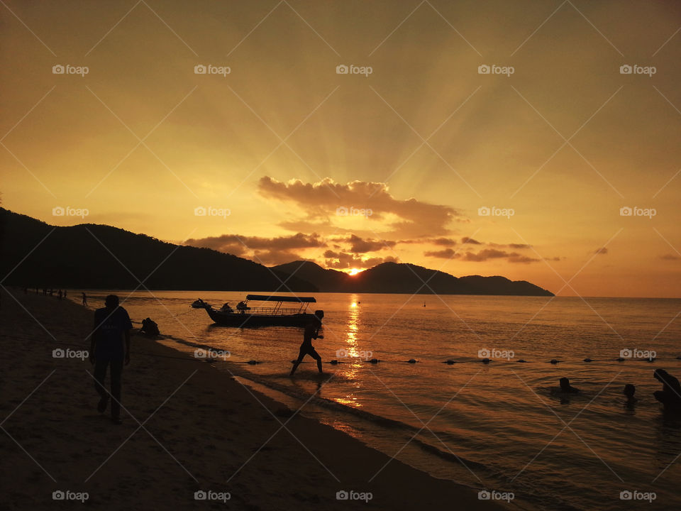 Breathtaking landscape orange sunset view with silhouettes of boat, hills and people enjoying the moment