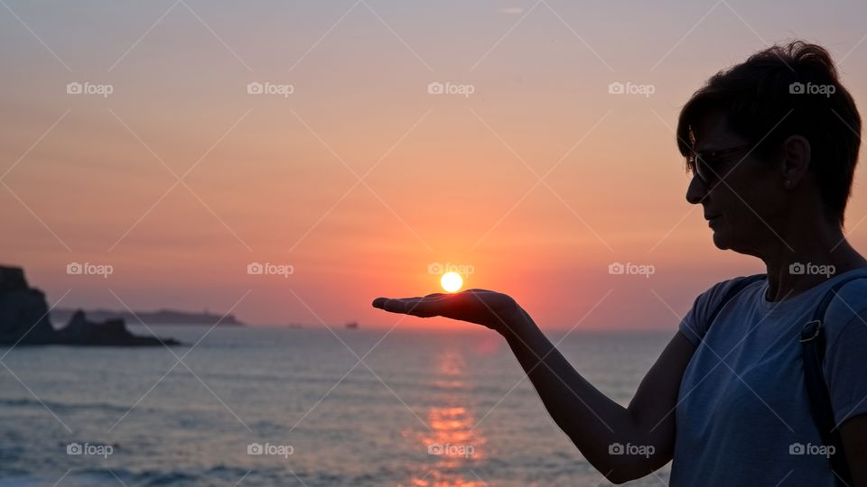 A woman holds the sun on her hand at sunset