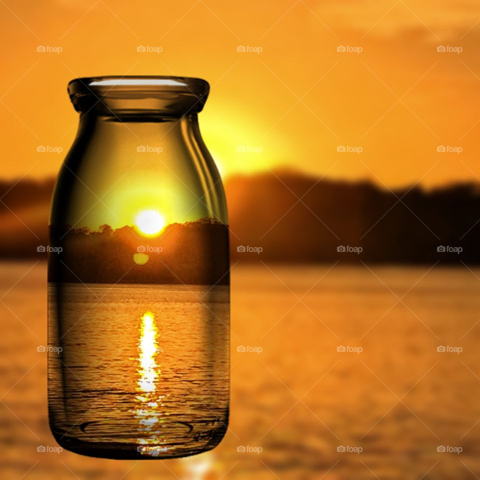 View of sunset through glass bottle