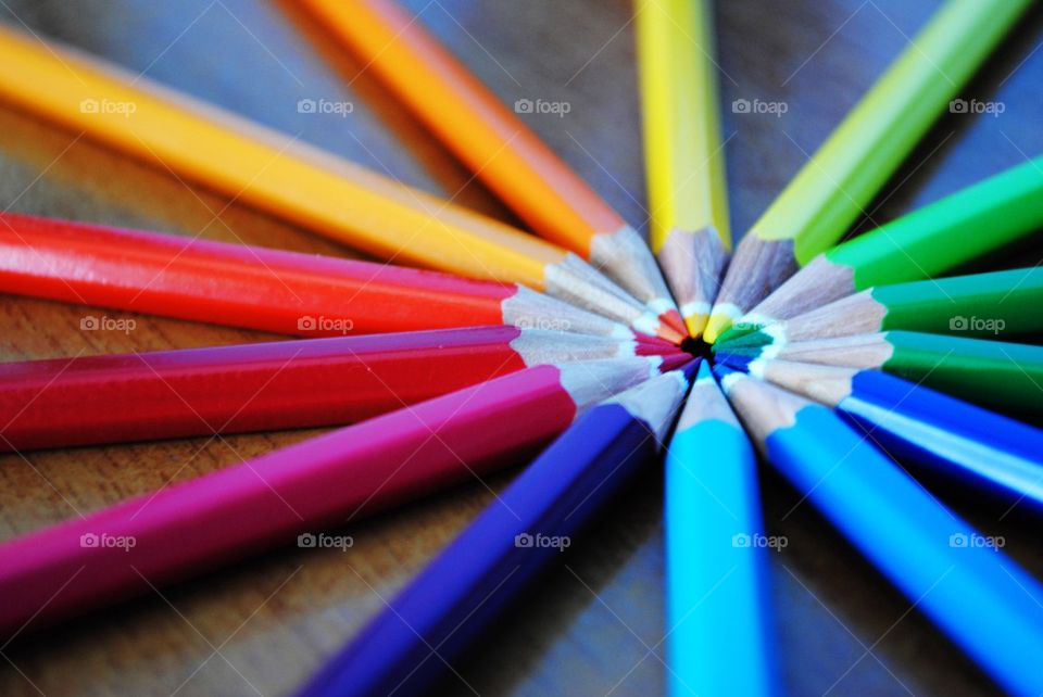 Arrangement of colorful pencils on wooden table